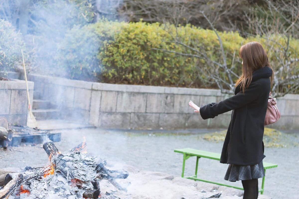 焚火で温まる人